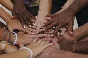 Hands of different people coming together